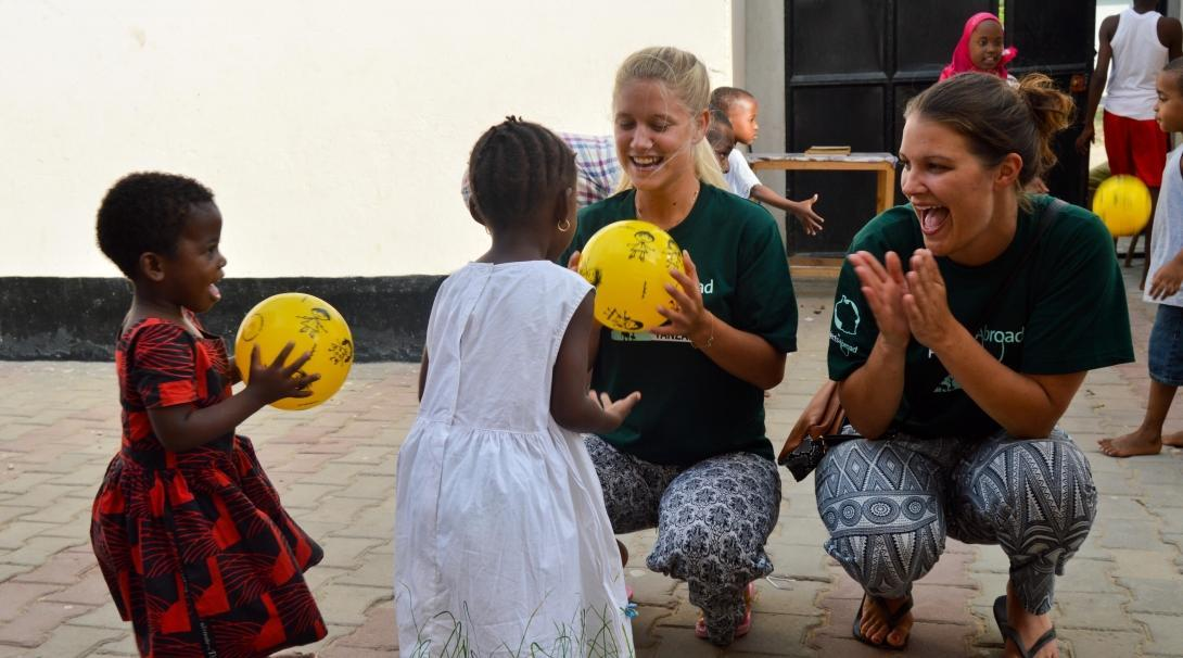 Projects Abroad volunteers with children in Tanzania play ball activities outside a kindergarten.